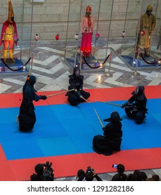 Almaty, Kazakhstan - Oct 7, 2017: Day of Japan Culture in Kazakh Museum. Four actors in samurai suits performing Kendo (fencing with bamboo sticks) surrounded with photographers. Selective focus