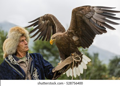 ALMATY,  KAZAKHSTAN - SEPTEMBER 12, 2016: Kazakh eagle hunter in traditional costumes holds his eagle in his hand and they look at each other in Almaty, Kazakhstan.