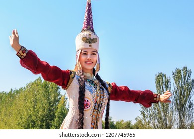 Almaty, Kazakhstan - September 16, 2018. Beautiful girl in national dress dances against the blue sky on a sunny day