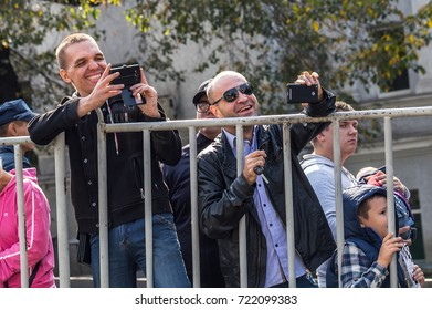 ALMATY, KAZAKHSTAN - SEPTEMBER 24, 2017: Viewers the Red Bull Soapbox Race 2017. Men laugh and take pictures on mobile phones.