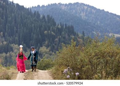 ALMATY, KAZAKHSTAN - SEPTEMBER 3, 2016: Kazakh couple in national costumes walk hand in hand in Almaty, Kazakhstan.