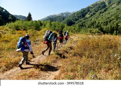 ALMATY REGION, KAZAKHSTAN - AUGUST 07, 2014: People hike to the Zhasylkol lake in Dzungarian Alatau mountains.