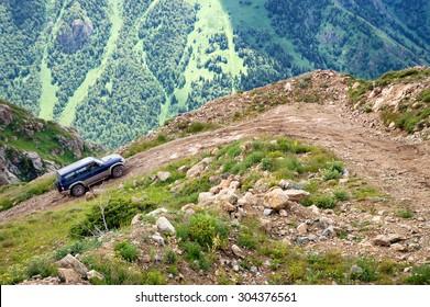 ALMATY REGION, KAZAKHSTAN - JULE 08, 2013: Jeep on a dangerous dirt road in the Kora gorge in Dzungarian Alatau.