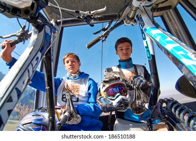 """ALMATY REGION, KAZAKHSTAN - OCT 13, 2013: Young sportsmen  S.Kuznetcov (N60) and A.Bospaev (N54) in the cable car, rise to start of competition at mountain bike sports event """"Red Bull Mountain Rage""""."""