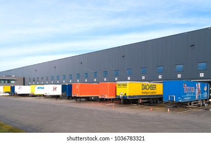 ALMELO, NETHERLANDS - FEBRUARY 4, 2017: Trailers in different colors in front of a large warehouse building