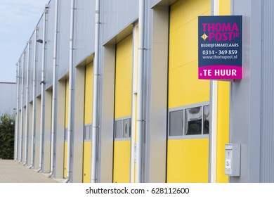 ALMELO, NETHERLANDS - JULY 9, 2016: For Rent (Te Huur) sign in front of a commercial warehouse with yellow roller doors