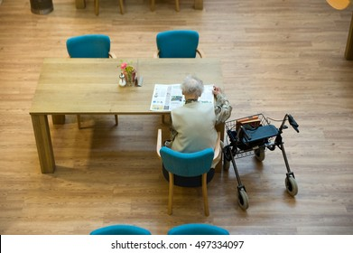 ALMELO, THE NETHERLANDS - JUNE 14, 2016: An elderly woman is reading a newspaper on the table of an elderly home.