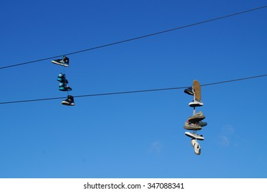 Almere, Flevoland, The Netherlands - December 4, 2015: Shoes and sneakers on wires above the street. Blue sky in the background.