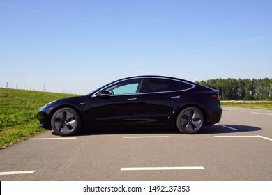 Almere, the Netherlands - August 24, 2019: Black Tesla Model 3 parked on a public parking lot. Nobody in the vehicle.