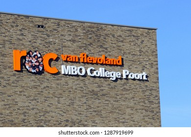 Almere, the Netherlands - Januari 18, 2019: Wall and logo of Dutch middle-level applied education school building, ROC Flevoland, MBO College Poort, against a clear blue sky.