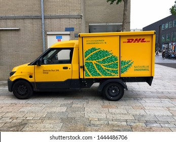 Almere, the Netherlands - July 6, 2019: Yellow electrical DHL delivery van parked by the side of the road. Nobody in the vehicle.