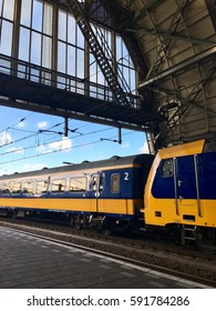 Almere, Netherlands - March 2, 2017: Yellow blue passenger electric train departures from Amsterdam Central Train Station
