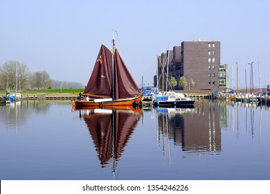 Almere, the Netherlands - March 29, 2019: Boat and building reflecting in the water of the harbor of Almere Haven.