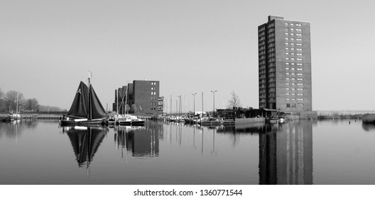 Almere, the Netherlands - March 29, 2019: Boat and building reflecting in the water of the harbor of Almere Haven. Black and white photo.
