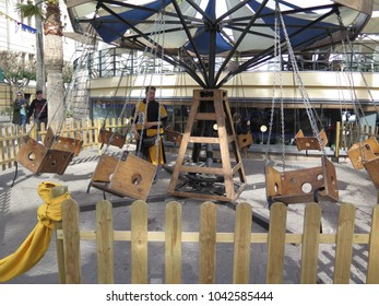 Almeria, Spain - February 10, 2018: Man operating hand crancked merry-go-round at Moroccan market