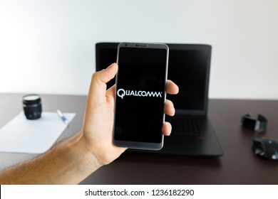 Almeria, Spain - November 11, 2018: Holding a LG G6 Android smartphone on hand with a Qualcomm PNG logo image on screen opened from the Gallery app on the phone covering the whole front display