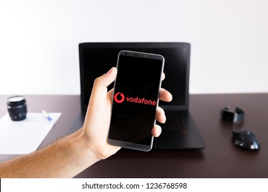 Almeria, Spain - November 11, 2018: Holding a LG G6 Android smartphone on hand with a Vodafone PNG logo image on screen opened from the Gallery app on the phone covering the whole front display