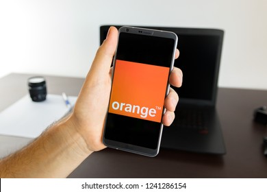 Almeria, Spain - November 11, 2018: Holding a LG G6 Android smartphone on hand with an Orange PNG logo image on screen opened from the Gallery app on the phone covering the whole front display