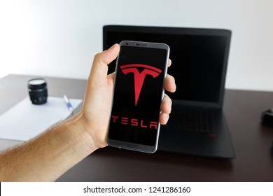 Almeria, Spain - November 11, 2018: Holding a LG G6 Android smartphone on hand with a Tesla PNG logo image on screen opened from the Gallery app on the phone covering the whole front display