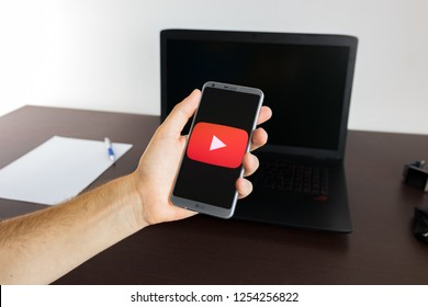 Almeria, Spain - November 11, 2018: Holding a LG G6 Android smartphone on hand with a YouTube PNG logo image on screen opened from the Gallery app on the phone covering the whole front display