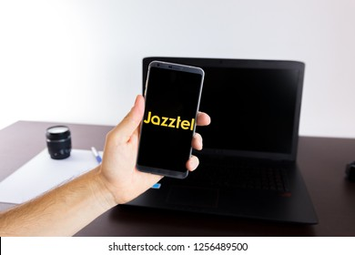 Almeria, Spain - November 11, 2018: Holding a LG G6 Android smartphone on hand with a Jazztel PNG logo image on screen opened from the Gallery app on the phone covering the whole front display