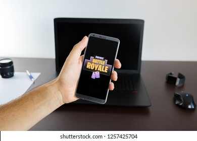 Almeria, Spain - November 11, 2018: Holding a LG G6 Android smartphone on hand with a Fortnite Battle Royale PNG logo image on screen opened from the Gallery app on phone covering the front display