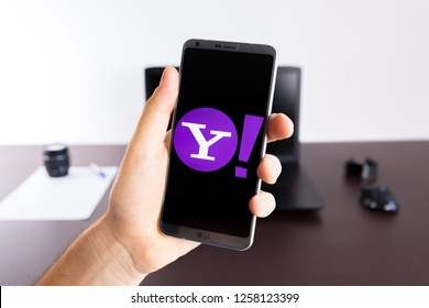 Almeria, Spain - November 11, 2018: Holding a LG G6 Android smartphone on hand with a Yahoo! PNG logo image on screen opened from the Gallery app on the phone covering the whole front display