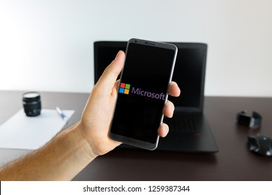 Almeria, Spain - November 11, 2018: Holding a LG G6 Android smartphone on hand with a Microsoft PNG logo image on screen opened from the Gallery app on the phone covering the whole front display