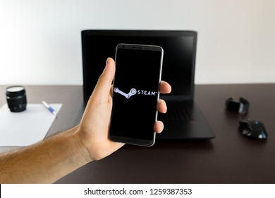 Almeria, Spain - November 11, 2018: Holding a LG G6 Android smartphone on hand with a Steam PNG logo image on screen opened from the Gallery app on the phone covering the whole front display