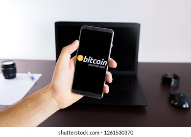 Almeria, Spain - November 11, 2018: Holding a LG G6 Android smartphone on hand with a Bitcoin Pay PNG logo image on screen opened from the Gallery app on the phone covering the whole front display