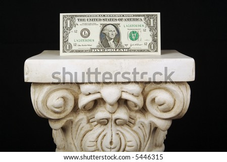 The Almighty Dollar - One dollar bill on a pillar with a black background.