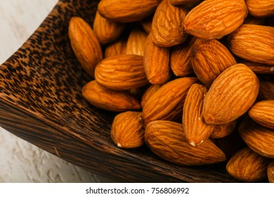 Almond in the bowl over the wooden background