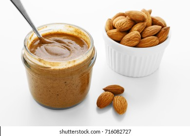 Almond butter with almonds on white background