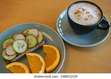 Almond butter toast with crisp cucumber and radish topping, orange slices, and cappuccino, served in retro midcentury modern dishware.