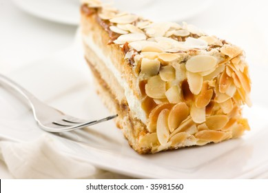 Almond cake. Piece of Cake on a Plate. Sweet food. Sweet dessert. White bakcground. Close up.