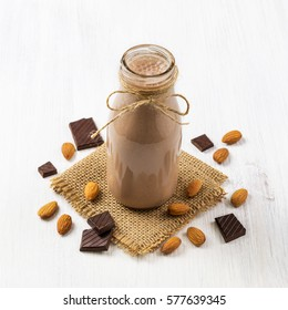 Almond chocolate smoothie. Healthy homemade milkshake in glass bottle on white wooden background. Health and diet concept