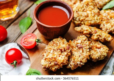almond crusted chicken tenders with tomato sauce on dark wood background. toning. selective Focus