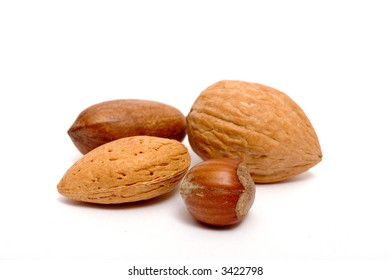 an almond, a hazelnut, a pecan and a alnut grouped together, isolated on white