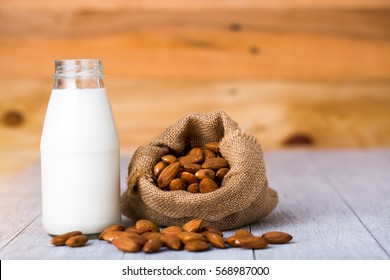 almond milk in bottle with almonds in sackcloth on woodene background with copy space
