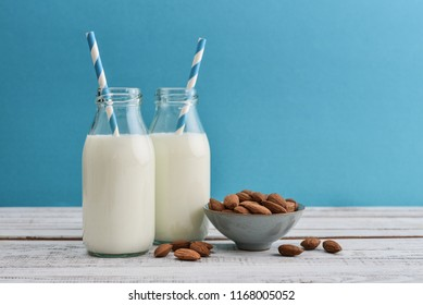 Almond milk in bottles with almonds and drinking straws on blue background