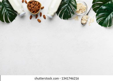 Almond milk in bottles and almond nuts with green leaves on white background, top view, copy space. Almond milk recipe mockup