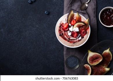 Almond milk bowl with strawberries and figs. Dark food photography concept. Flatlay with copy space