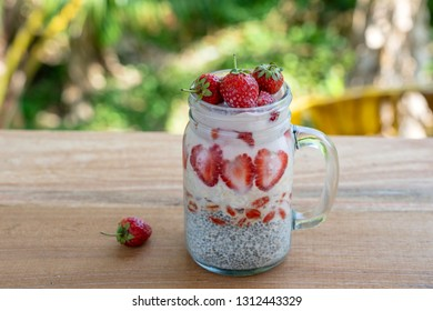 Almond milk chia pudding with fresh red strawberries, goji berries and oat flakes in a glass jar mug. Vegan raw breakfast. Chia seeds and fresh cut fruits and berries dessert, close up