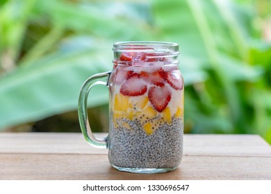 Almond milk chia pudding with fresh strawberries and mango in a glass jar mug. Vegan raw breakfast. Chia seeds and fresh cut fruits and berries dessert, close up
