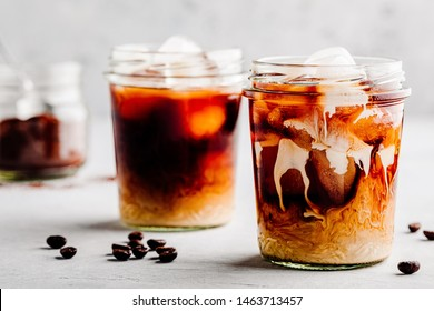 Almond Milk Cold Brew Coffee Latte in glass jar on a gray stone background