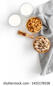 Almond milk in glass with almonds on white background top view copyspace