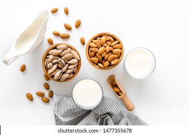 Almond milk in glass with almonds on white background top view