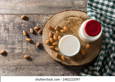 Almond milk in glass and bottle on wooden table. Top view. Copyspace