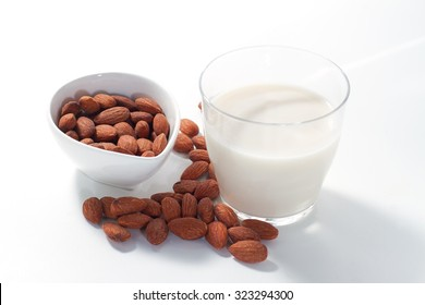 Almond milk in glass with almond nuts in glass bowl isolated on white
