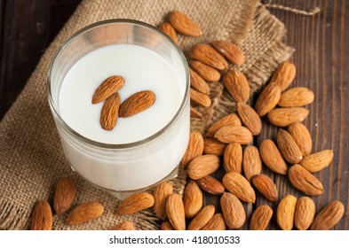 Almond milk in a glass with almond nuts on a wooden table. Healthy food and drink concept.